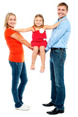 Baby girl sitting on outstretched arms of her parents
