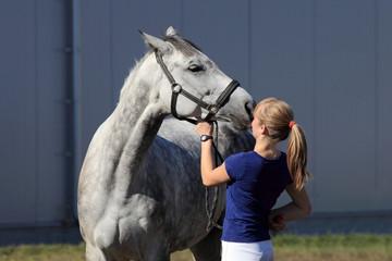 Piękna dziewczyna, dżokejka karmi konia jabłkiem.