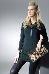 fashionable young woman with purse posing light background