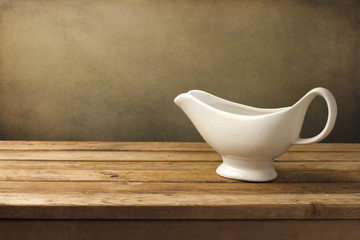 White gravy boat on wooden table over grunge background