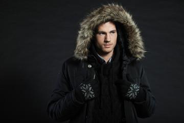 Handsome man dark winter fashion. Studio shot. Wearing hoody.