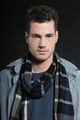 Handsome man dark winter fashion. Studio shot. Wearing scarf.