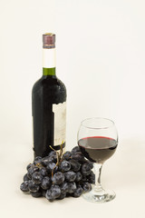 A glass of red wine and grapes.