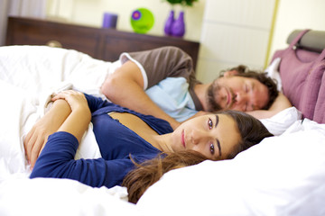 Sad woman in bed with sleeping husband