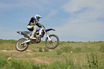 MX rider sitting on the motorbike in the air