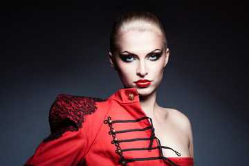 serious blonde woman in red jacket