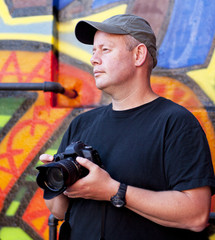 photographer with camera near graffiti background