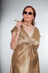 Portrait of good looking senior woman smoking a cigarette.