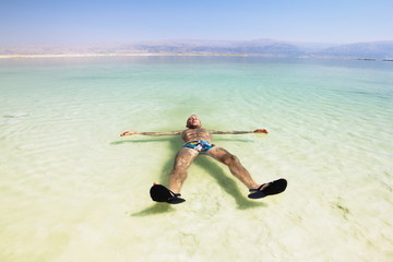 A man rests his hand on the water of the dead sea in Israel