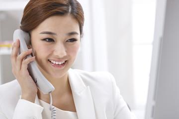 Businesswoman using fixed phone