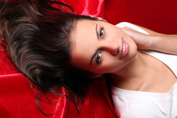 Closeup of beautiful and young brunette face lying on red matter