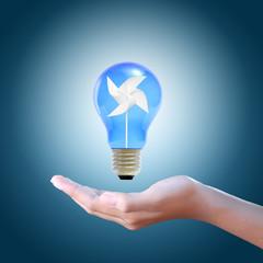 Paper windmill in a blue light bulb on women hand