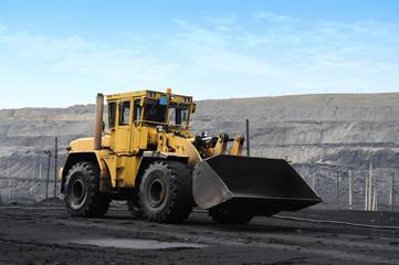 Yellow bulldozer goes in the coal mine. Желтый бульдозер едет в угольном карьере
