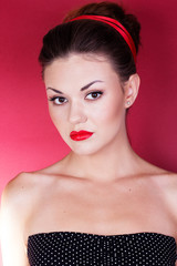 Pin-up girl with red ribbon in her hairs