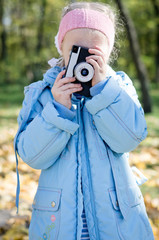 Small girl playing with an slr camera