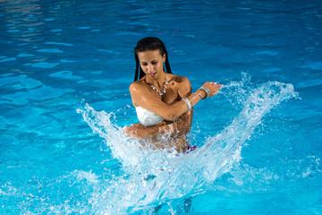Young beautiful woman splashing water