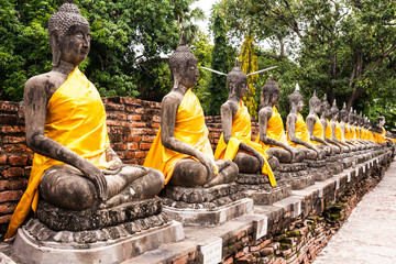 Stone Buddha statue in row