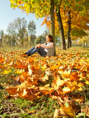 Girl sitting on the yellow leaves carpet