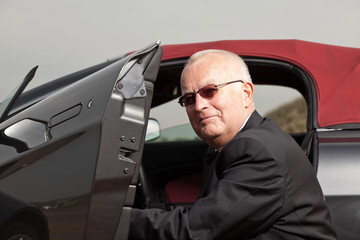 Senior good looking happy retired man with his sports car.