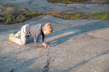Kleiner Junge untersucht prähistorische Felszeichnungen
