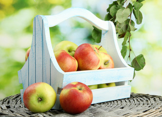 juicy apples with leaves in wooden basket, on green background