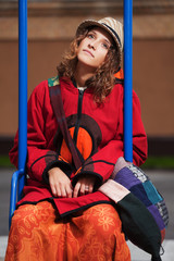 Young hippie woman sitting on the swing