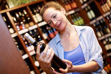 Ältere Frau kauft Wein