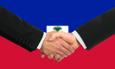 The Haiti flag and business handshake.