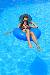 Woman in bikini and hat is in the water