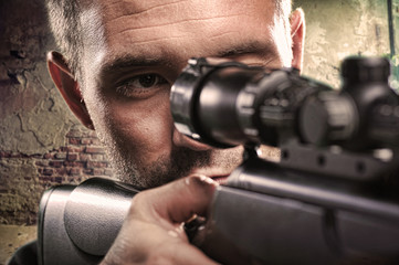Portrait of serious man aiming with gun
