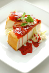 сheesecake with strawberry sauce on a plate.