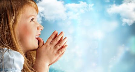 Portrait of young smiling praying girl in blue dress against sky