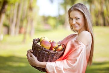Obraz Uśmiechnięta kobieta z koszem jabłek - fototapety do salonu