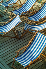 Row of empty blue and white striped beach chairs
