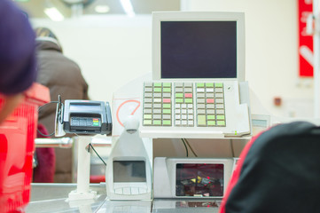 Cash-desk with terminal in supermarket. Customers on background