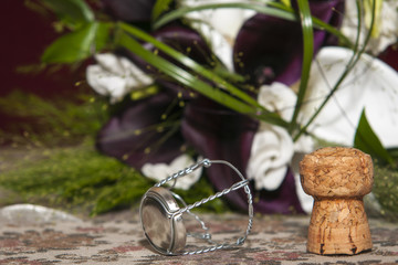 standing cork of bottle with metal in front of bridal bouquet