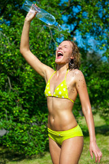 Young woman splashing herself with water