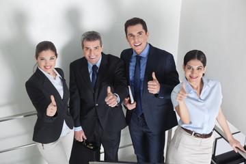 Lachende Geschäftsleute halten Daumen hoch