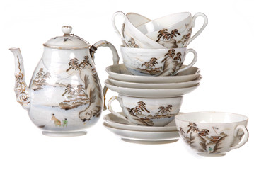 beautiful porcelain tea service stacked together on white backgr