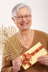 Elderly lady with christmas present smiling