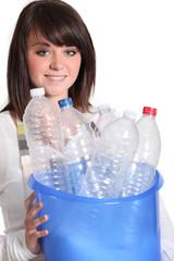 Girl carrying bucket of empty plastic bottles