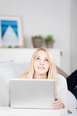 blonde frau liegt mit laptop auf dem sofa