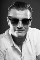Macho man with short brown hair wearing sunglasses.