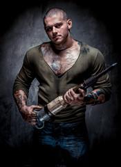 Muscular tattooed man with jackhammer posing indoors