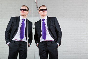 Cool good looking business man with sunglasses against mirror.