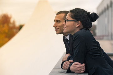 Couple of businessman and woman looking forward outdoors.