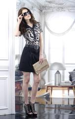 fashion model in modern dress holding little purse posing