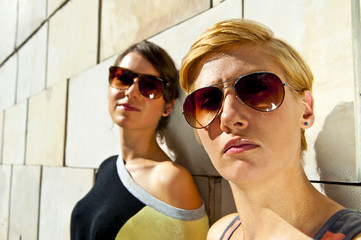Two  beautiful woman with sunglasses on stone wall background
