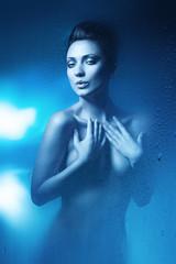 erotic brunette woman in dark blue shower