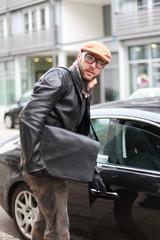 Mann mit Tasche steigt ins Auto